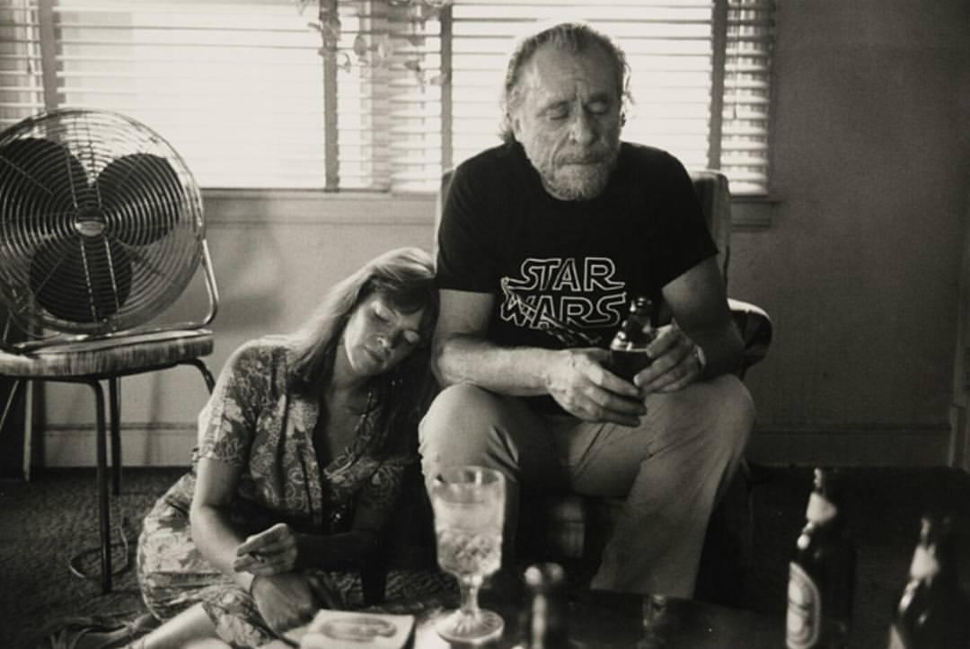 Sėdi ant sofos su buteliu rankoje, šalia ant žemės prisiglaudusi sėdi jo žmona.