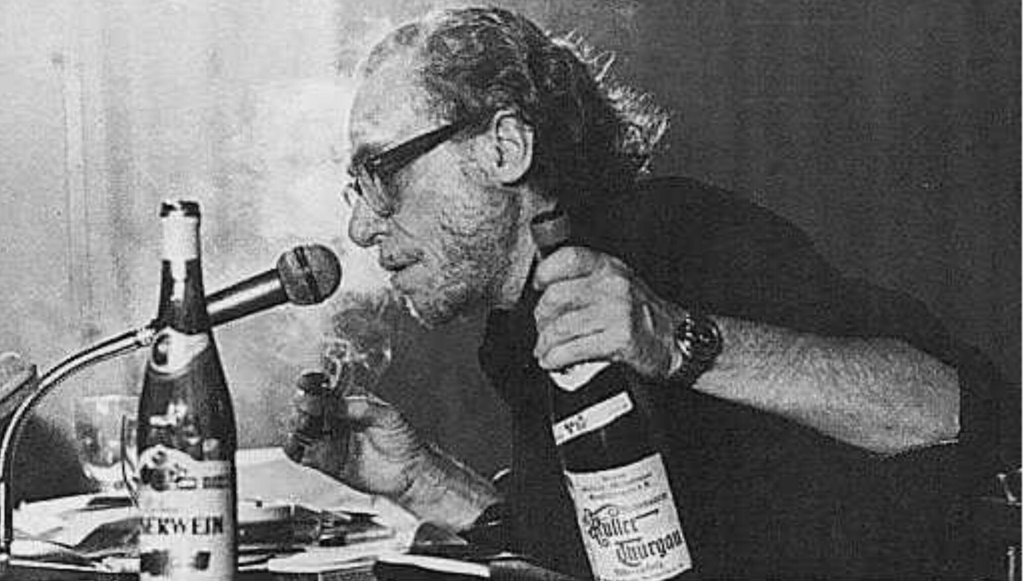 Su buteliu kalba į mikrofoną.