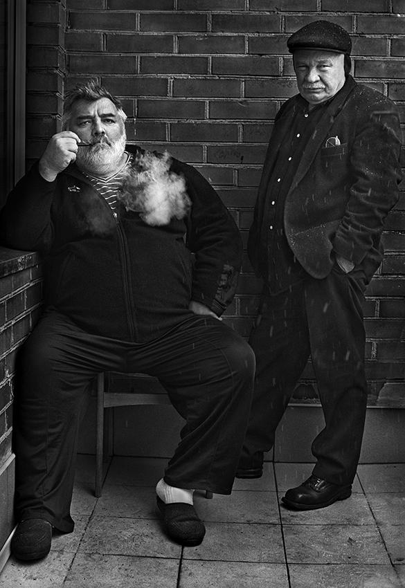 A. Bumblauskas sėdi ir rūko pypkę, P. Repšys stovi šalia.