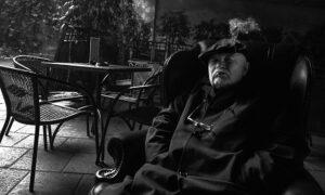 Sėdi fotelyje ir rūko.