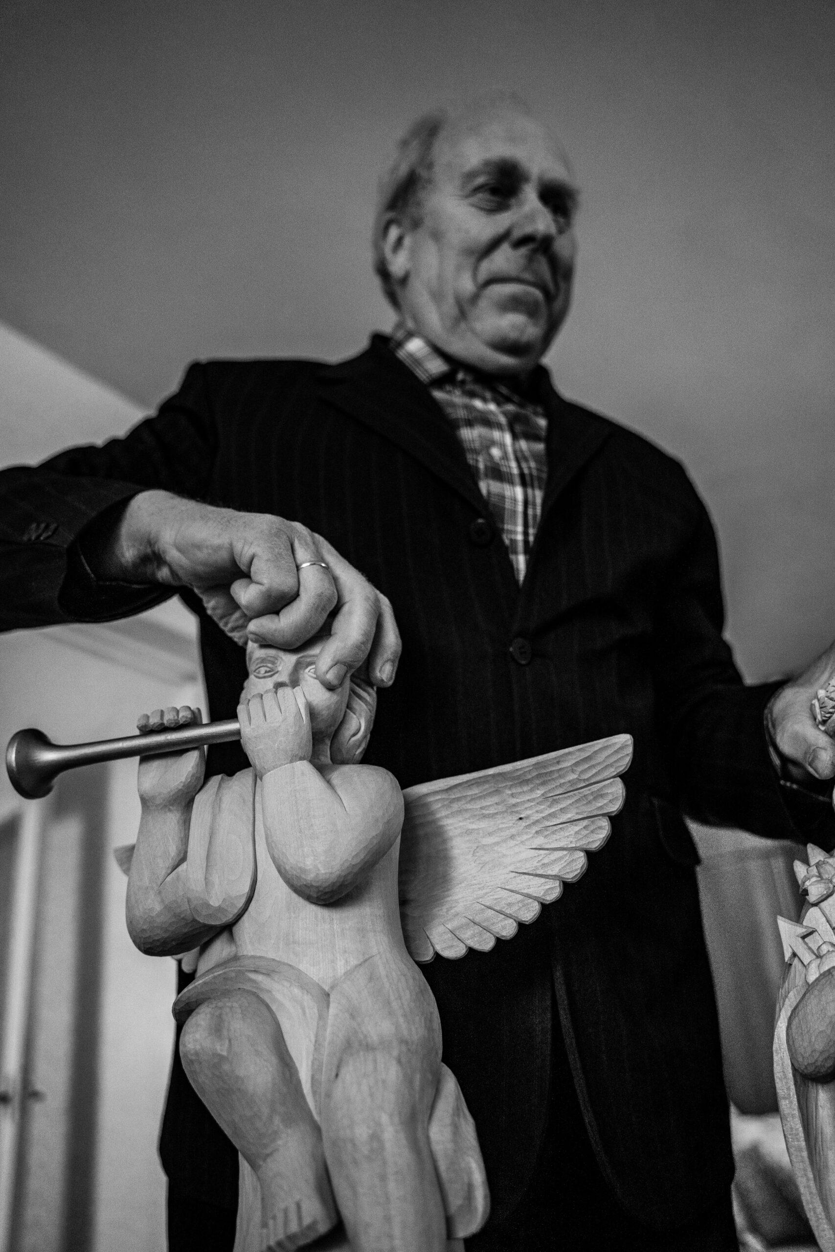 Su angelo skulptūra rankose.