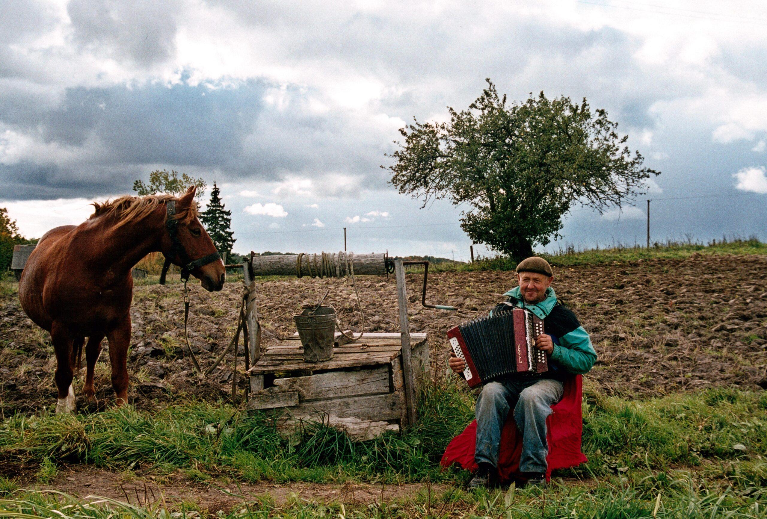 Žmogus groja armonika vienkiemyje.
