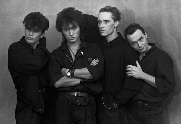 Keturi asmenys, apsirengę juodai.