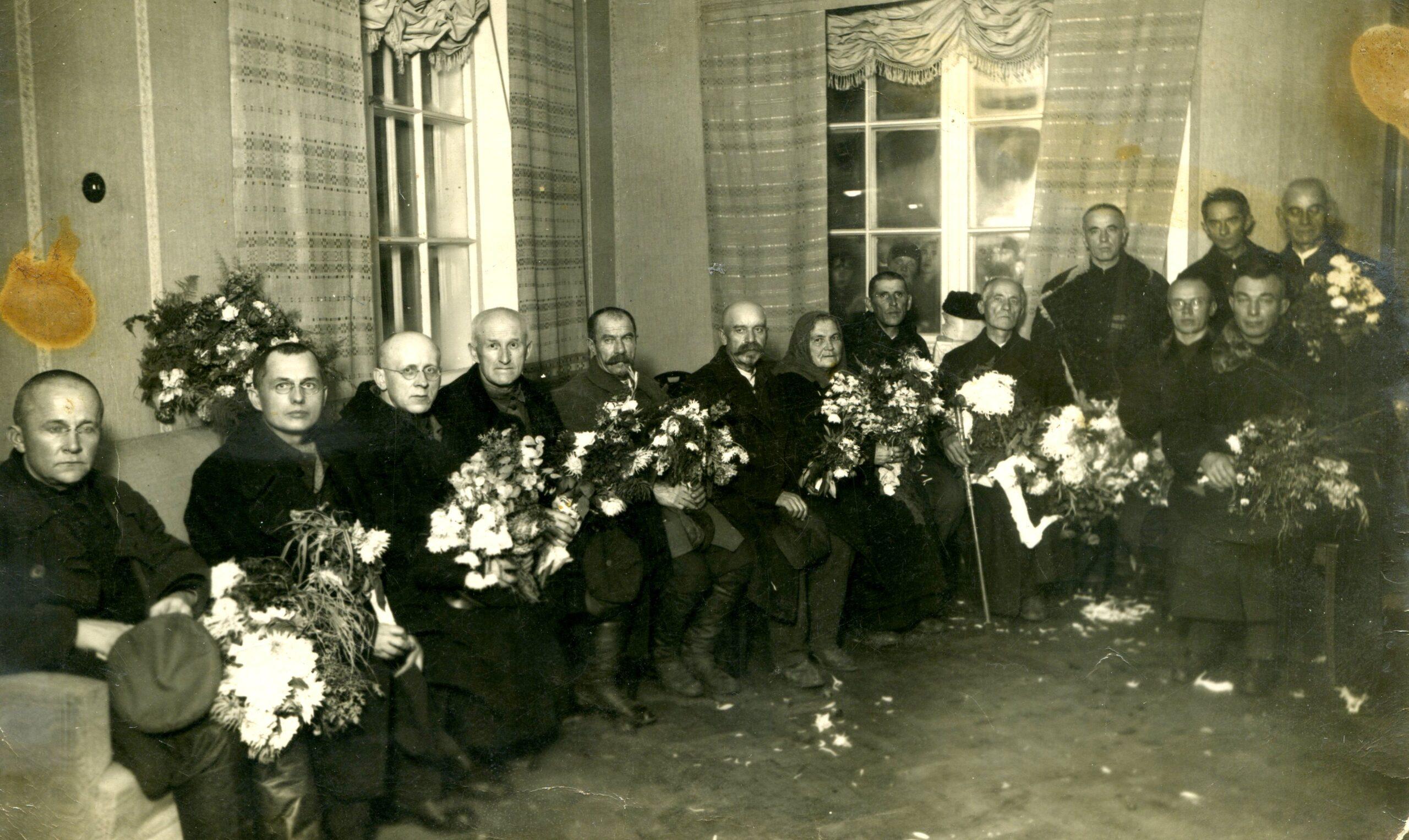 Potiniai kaliniai sėdi ant kėdžių su gėlėmis rankose.