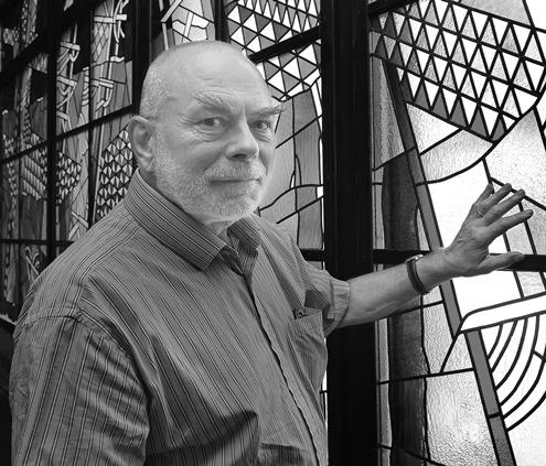 Algirdas Dovydėnas stovi prie savo vitražo.