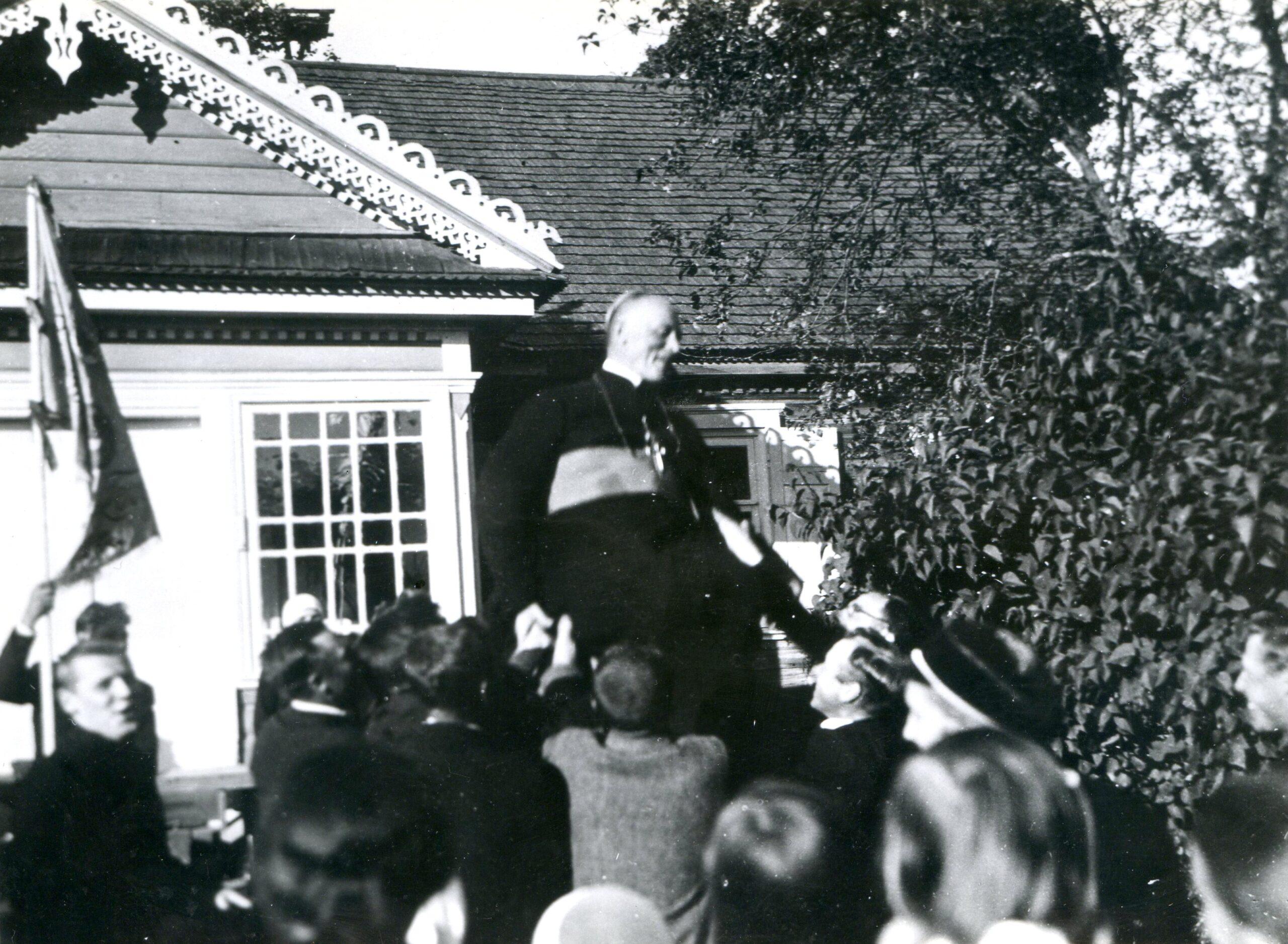 Žmonės ant rankų kilnoja vyskupą.