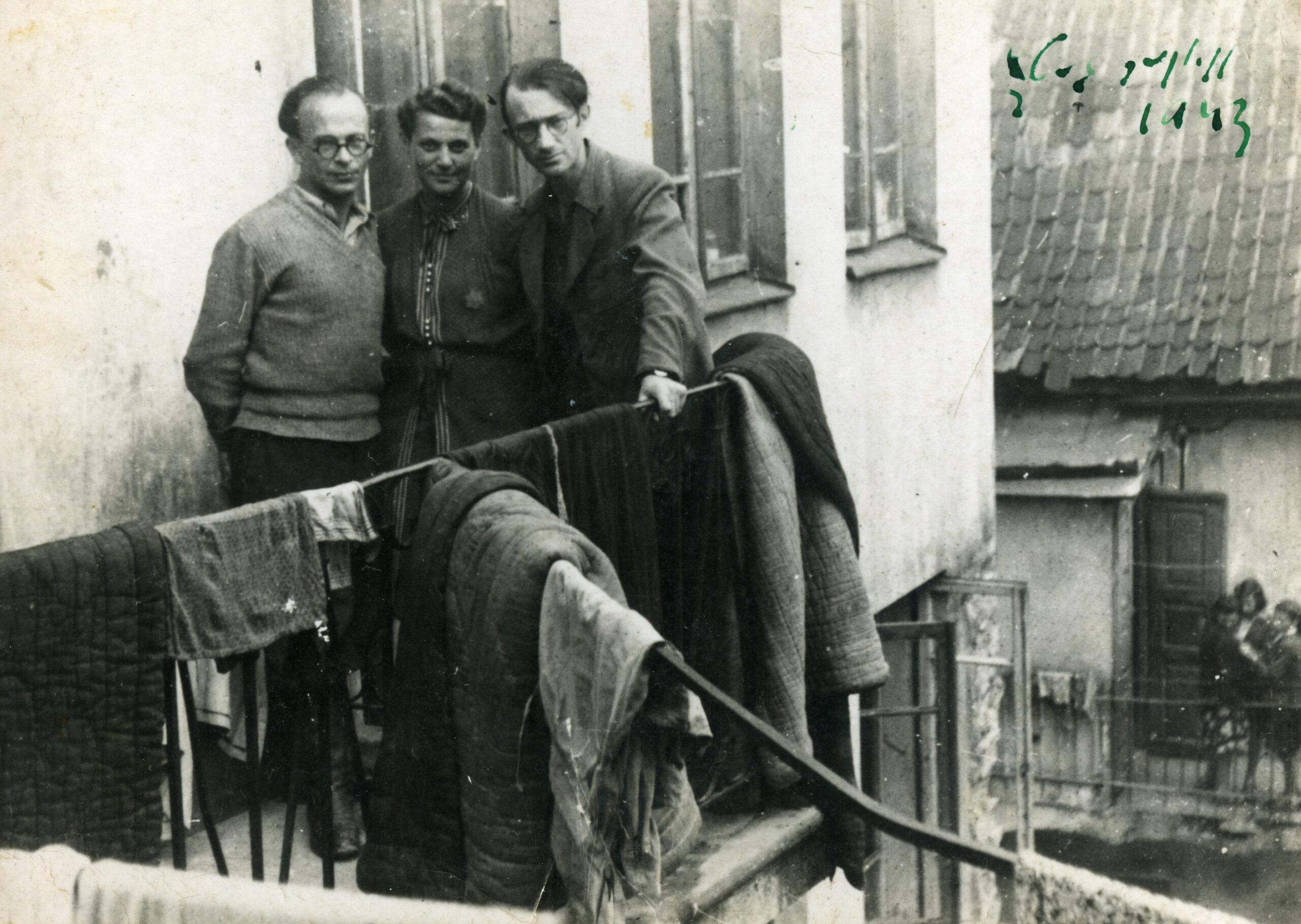 Du vyrai ir viena moteris stovi balkone.
