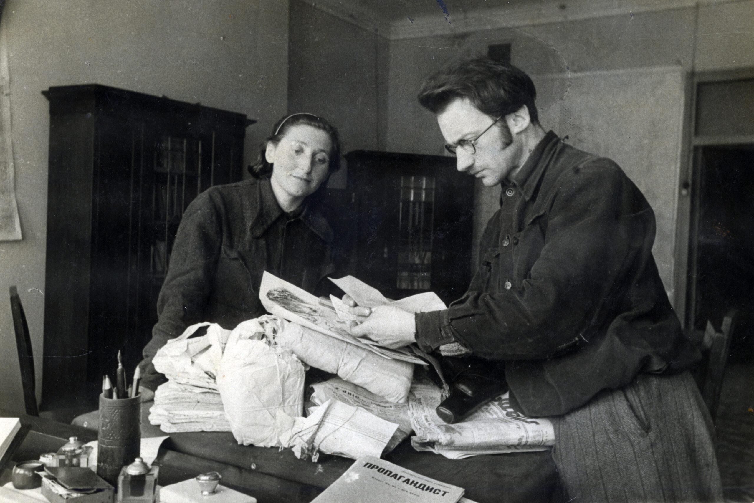 Vyras ir moteris rūšiuoja dokumentus.