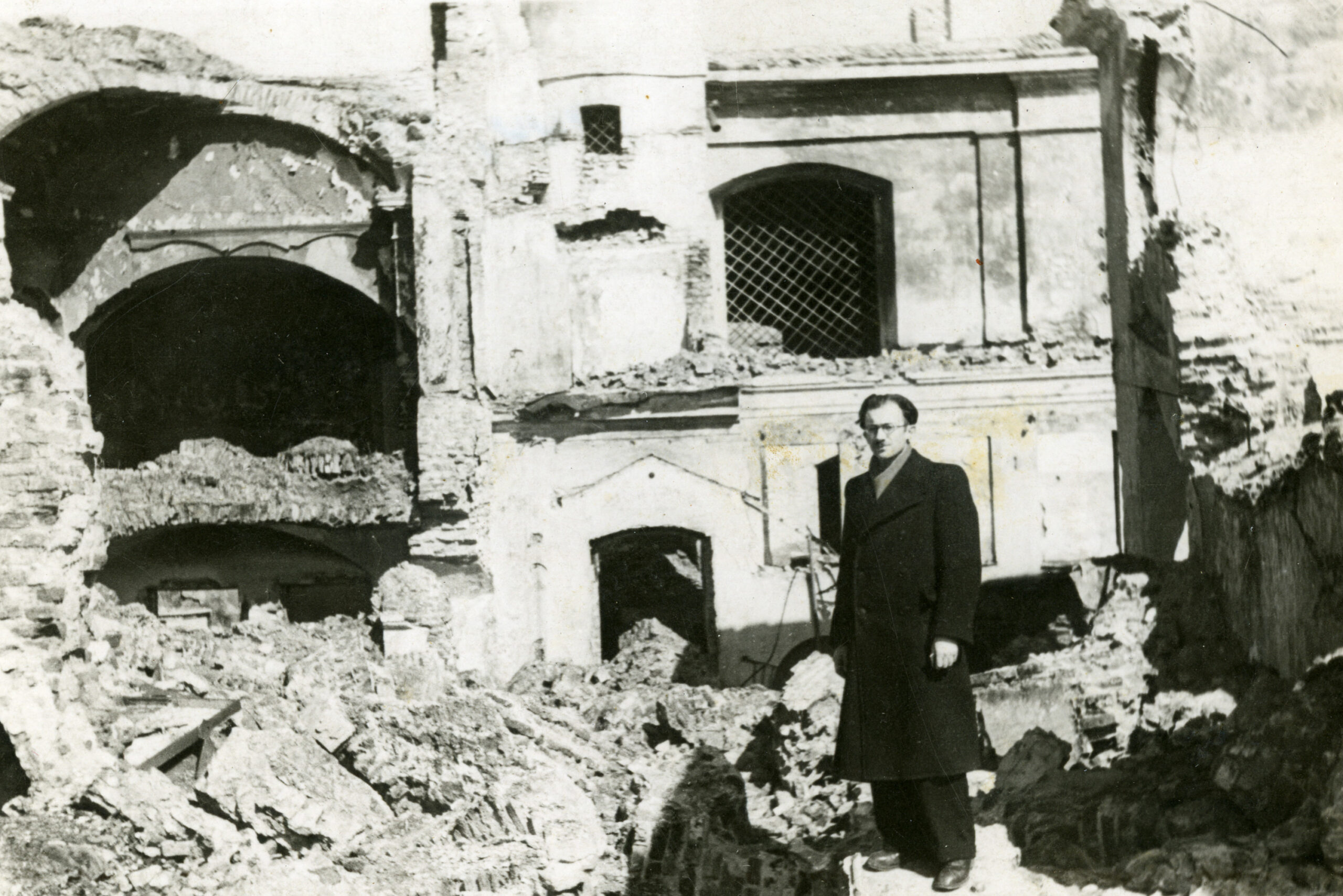 Žmogus stovi prie griuvėsių.