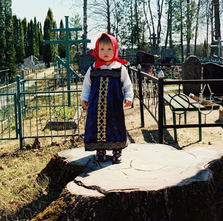 Mergaitė prie kapinių.