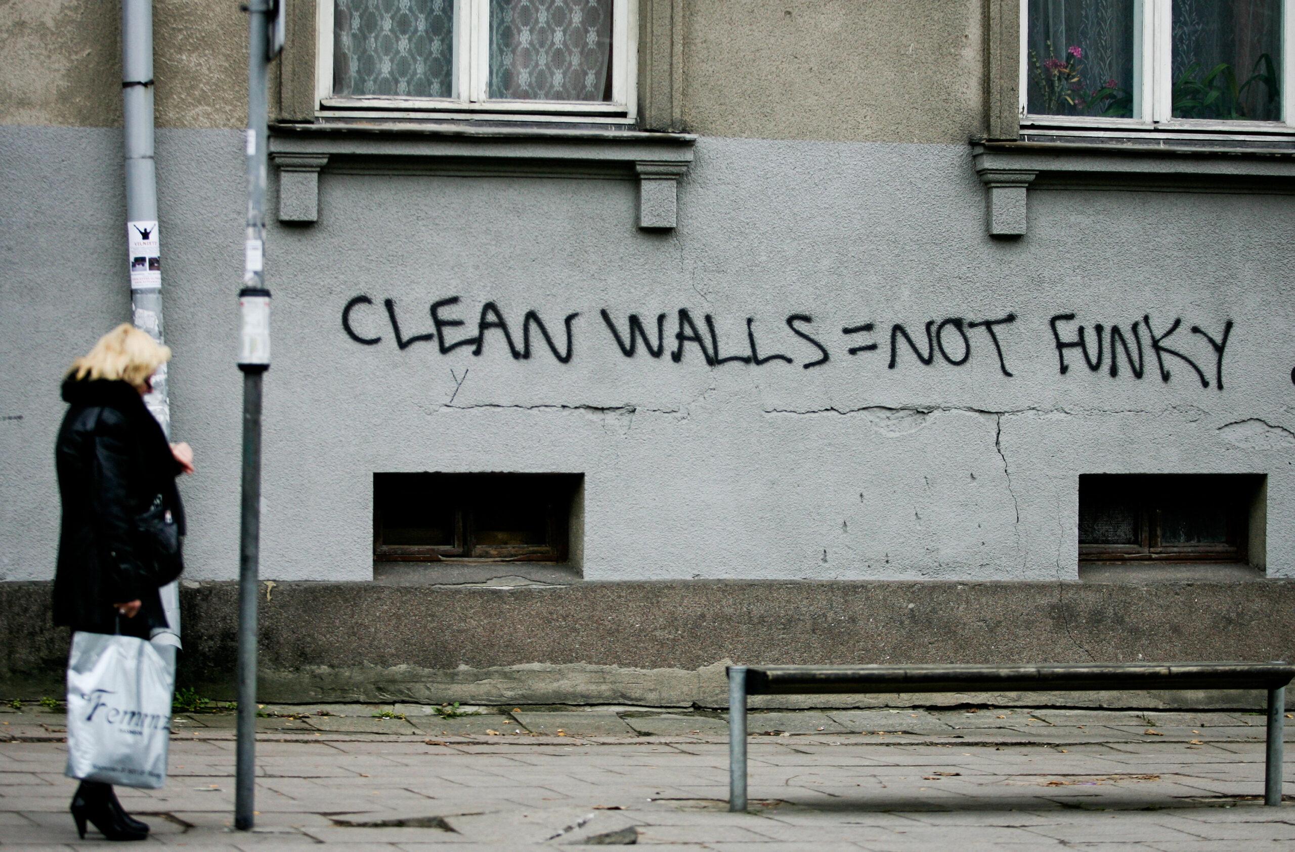 "Užrašas ""Clean walls = not funky"" ant namo sienos."