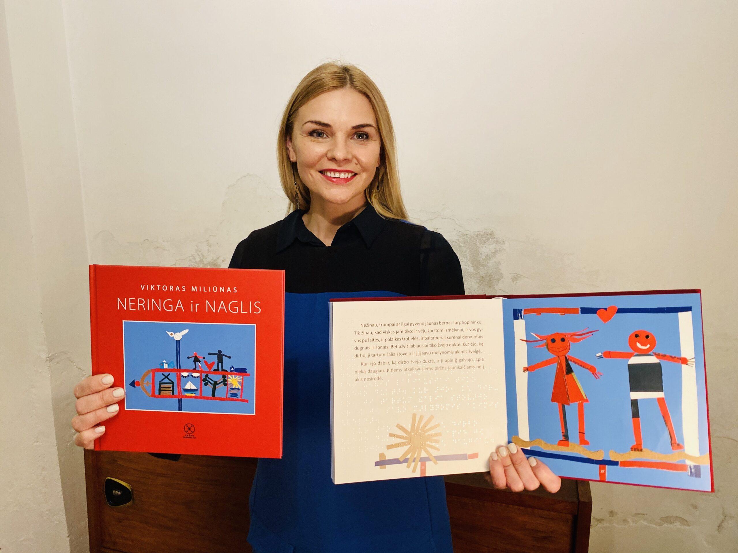 """Eglė Jokužytė šypsodamasi rankose laiko dvi knygas. Kairėje nuotraukos pusėje rankoje atsukta viršeliu knyga, kuri yra skirta tik regintiems vaikams. Viršelyje baltomis raidėmis užrašyta: Viktoras Miliūnas """"Neringa ir Naglis"""" – ir viduryje Reinoldo Kelpšos iliustracija su vėtrungės vaizdu. Kitoje rankoje atversta knyga, pritaikyta ir neregiams. Viename puslapyje tekstas, parašytas reginčiųjų ir Brailio raštu, kitoje pusėje – iliustracija su Neringos ir Naglio personažais, tarp jų fone širdis."""