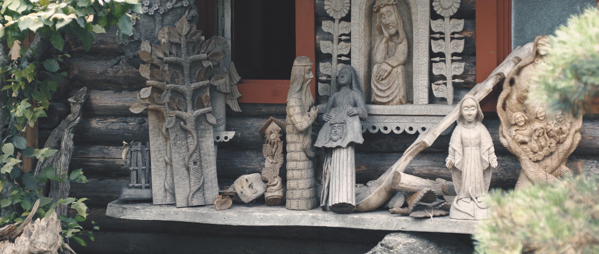 Medžio skulptūros ant suolo.