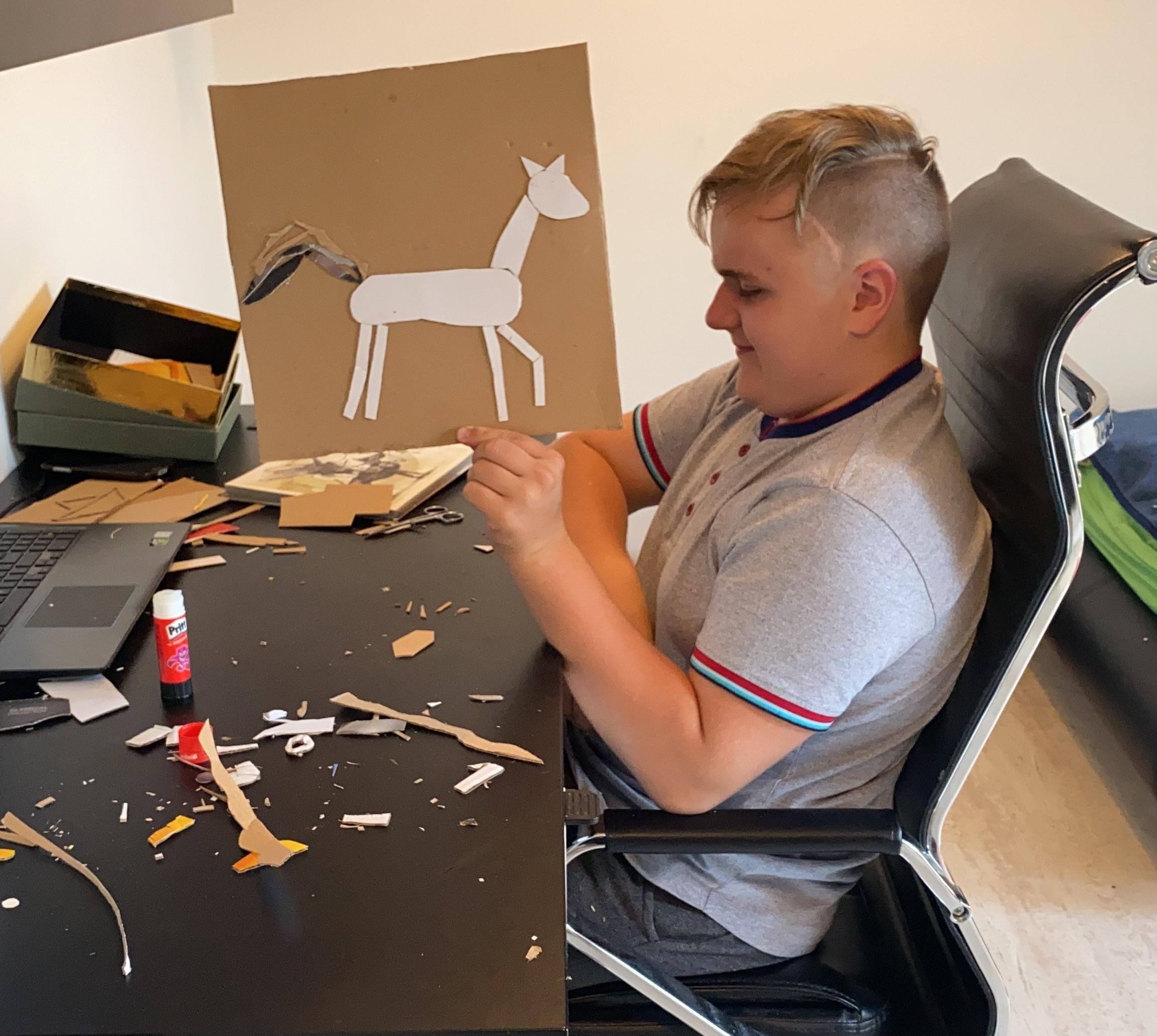 """Reinoldas Kelpša. Nuotrauka daryta iliustracijų kūrimo proceso metu. Jaunas vaikinas sėdi pasisukęs šonu prie darbinio rašomojo stalo, ant kurio yra klijai, žirklės ir popieriaus atraižos. Rankoje menininkas laiko iškeltą dar nebaigtą kūrinį knygai """"Neringa ir Naglis"""" – ant kartono lapo pavaizduotas bėgantis šviesus žirgas su iškelta uodega."""