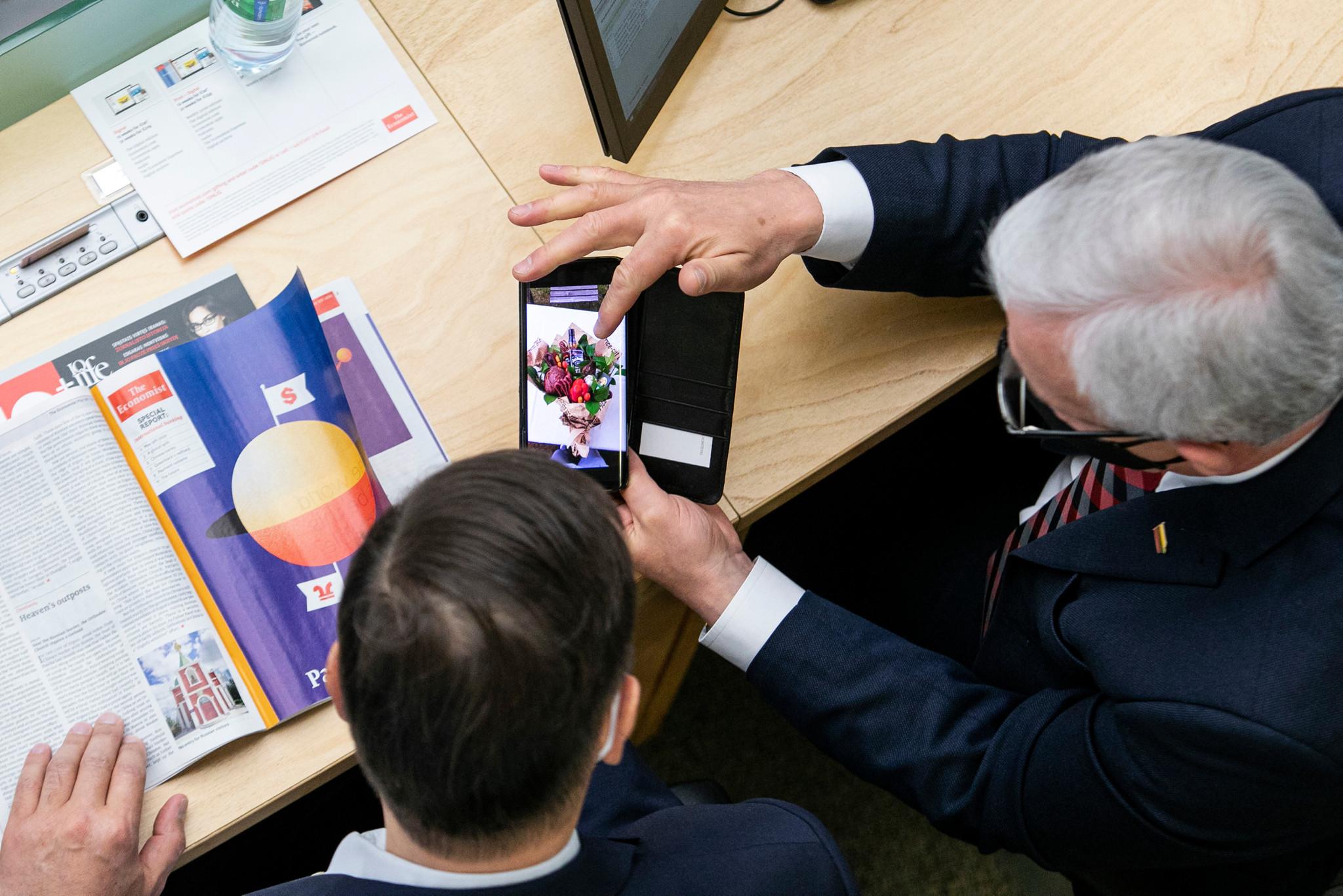 Seimo nariai žiūri į išmanųjį telefoną