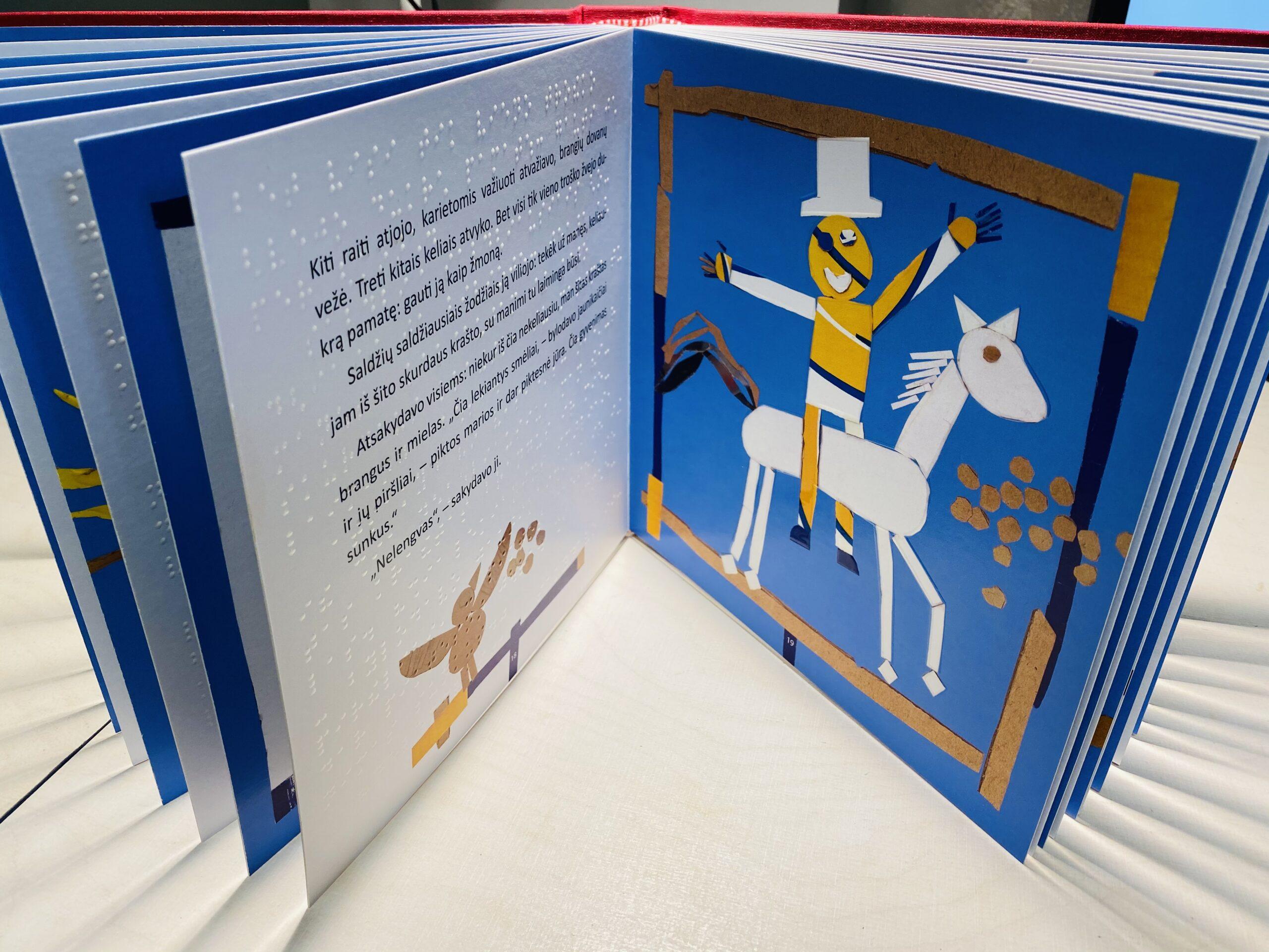 """3. Nuotraukoje pastatyta knyga """"Neringa ir Naglis"""" su atverstu vaizdu. Vienoje pusėje tekstas reginčiųjų ir Brailio raštu, kitoje – iliustracija, kurioje pavaizduotas ant žirgo sėdintis raitelis su iškeltomis rankomis ir šypsena, o ant jo galvos cilindro formos skrybėlė."""