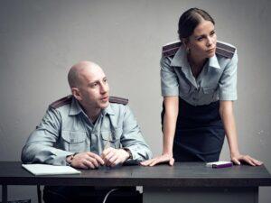 "Marius Repšys sėdi prie stalo su milicininko forma spektaklyje ""Žmogus iš Podolsko""."