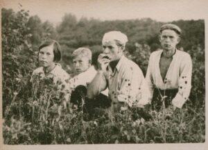 Alfonsas Nyka-Niliūnas groja sėdėdamas pievoje lūpine armonikėle. Šalia – broliai ir sesuo.