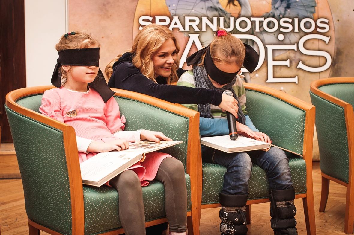 Nuotraukoje trys žmonės: dvi sėdinčios mergaitės raiščiais užrištomis akimis, ant kelių pasidėjusios atverstas knygas, kurias liečia rankomis. Už jų nugaros pritūpusi E. Jokužytė su mikrofonu kalbina vieną iš mergaičių.