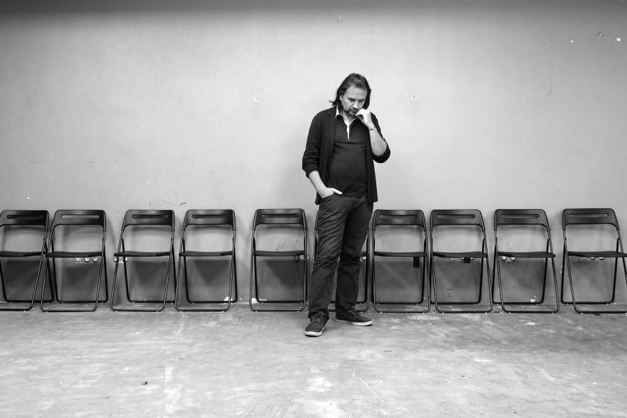 Oskaras Koršunovas stovi prie sienos.