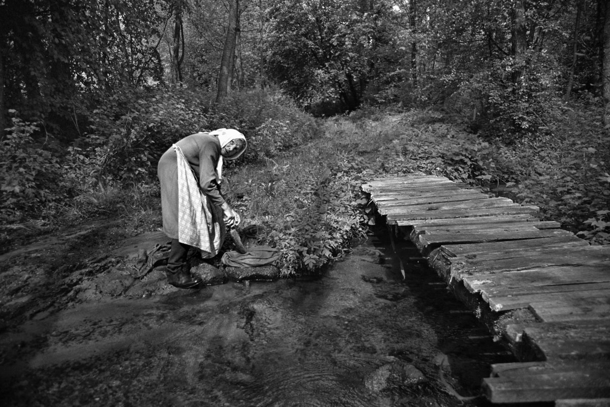Moteris prie upės plauna.