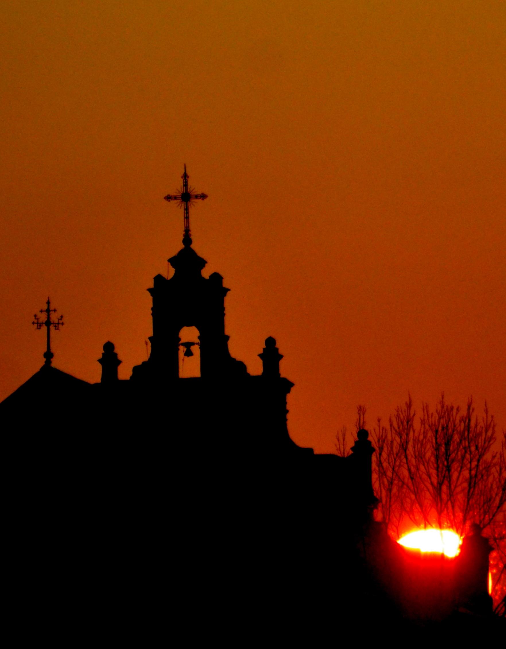 Kaitrą pranašaujančiame raudoname danguje matyti bažnyčios bokšto su kryžiais siluetas.