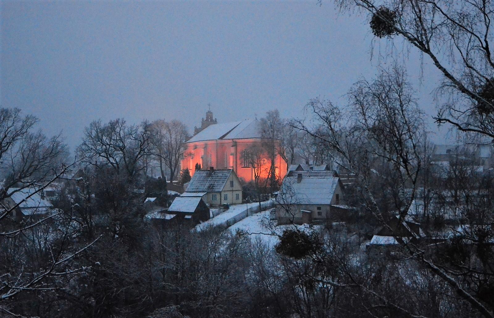 Apšviesta bažnyčia žiemos peizaže.