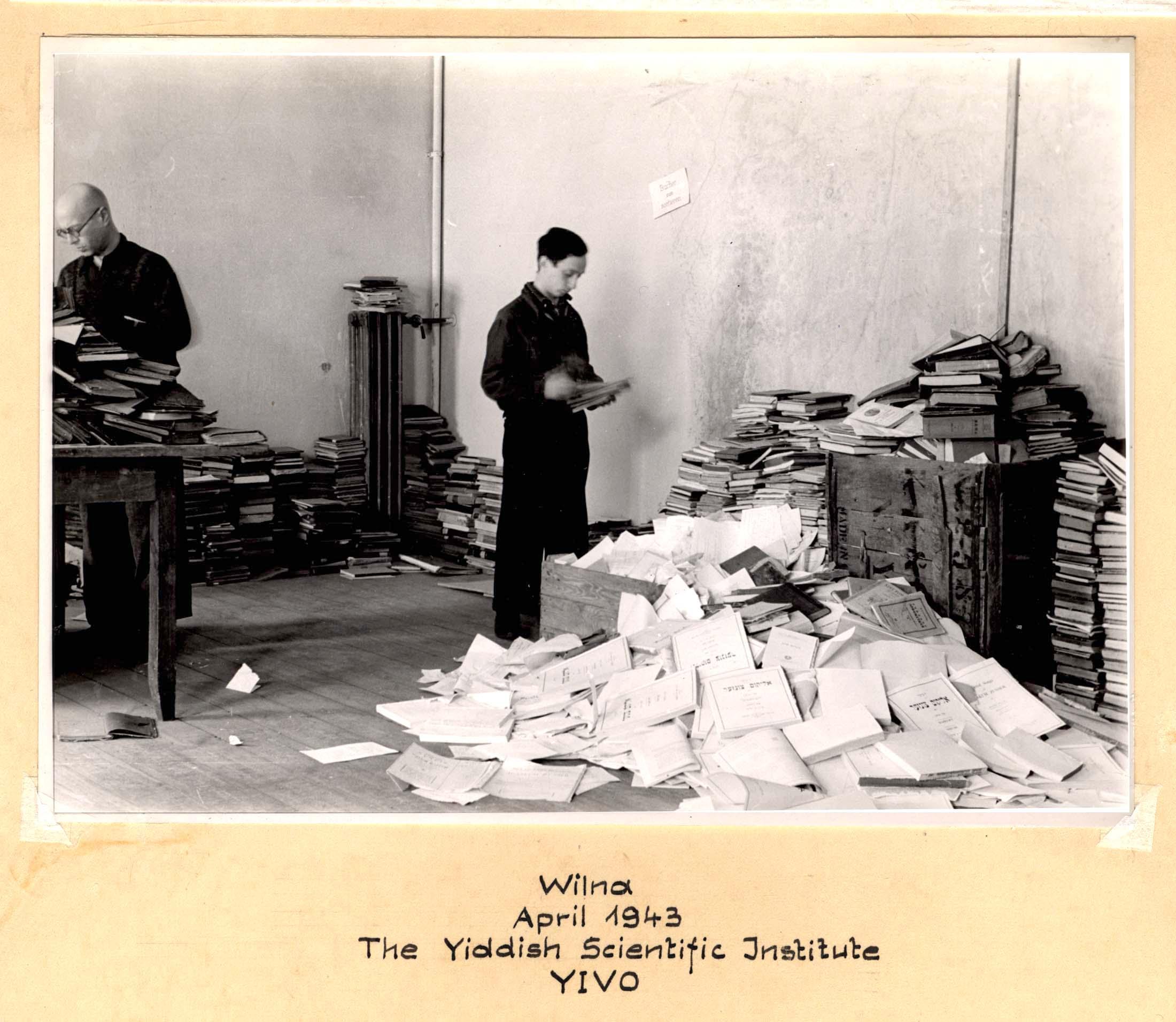 Vyrai rūšiuoja dokumentus.