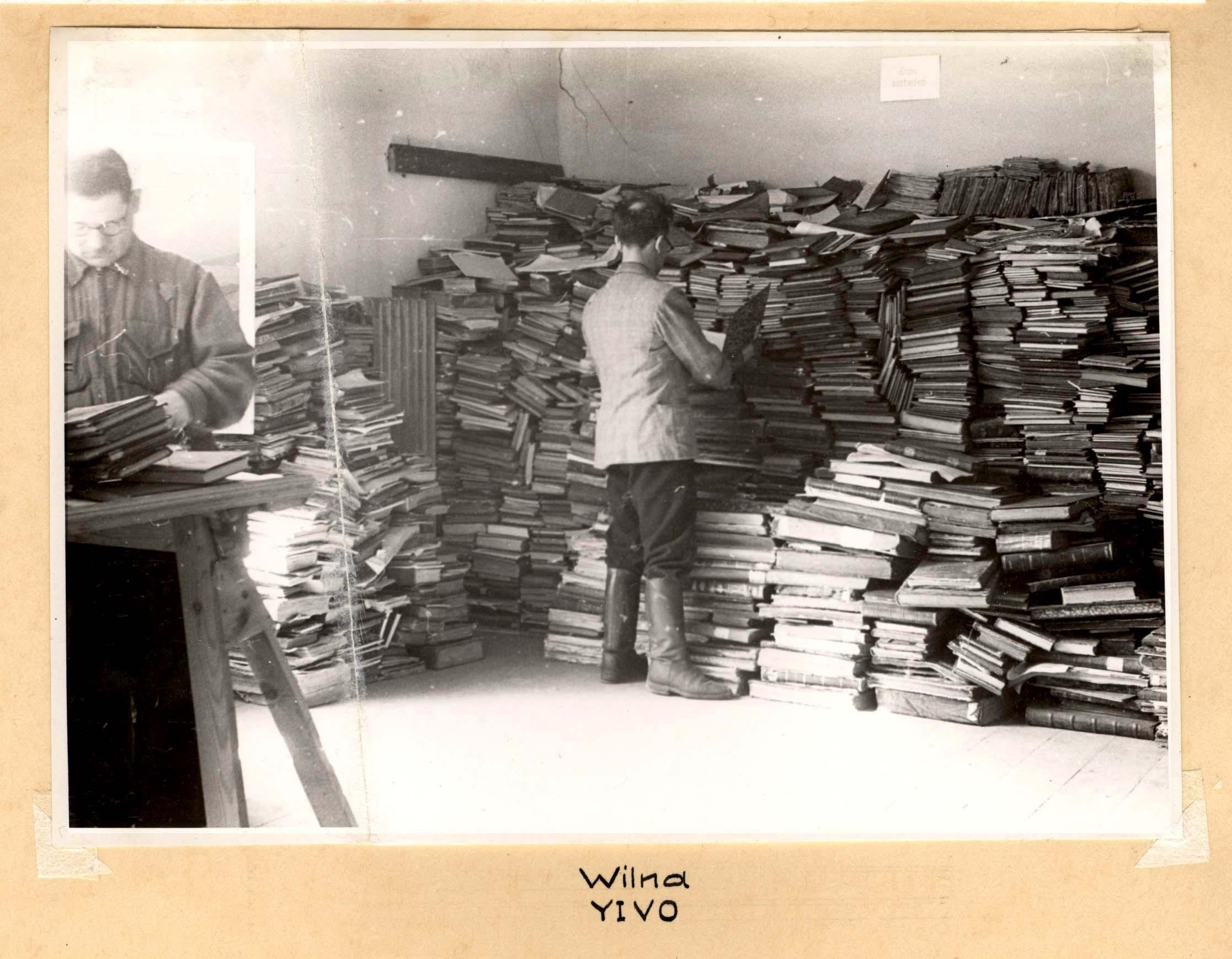 Vyrai rūšiuoja knygas.