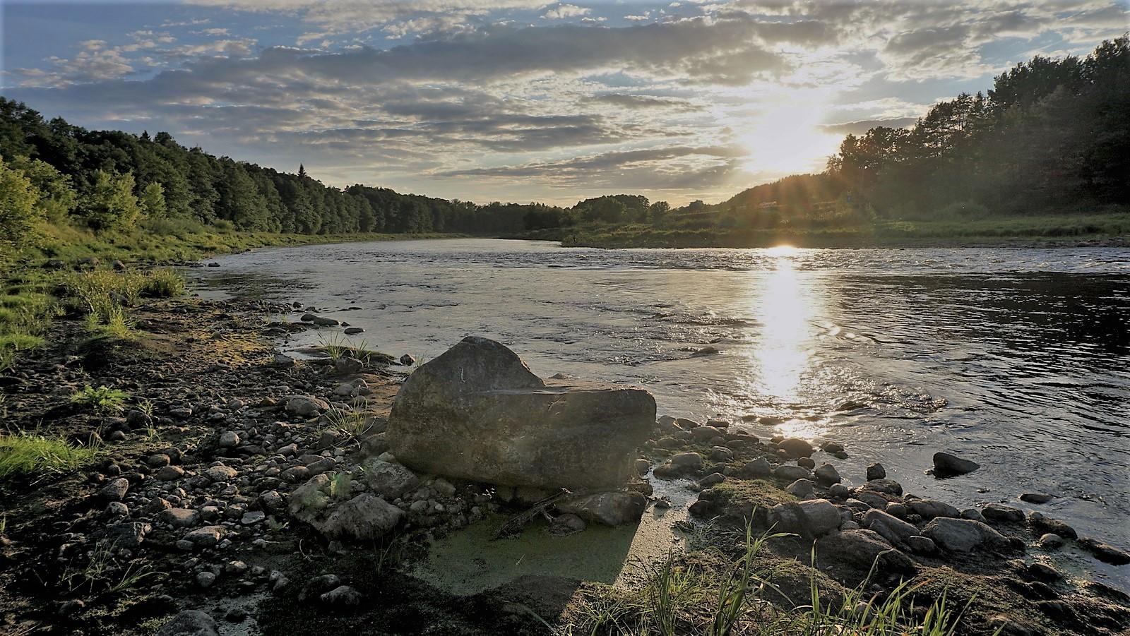 Akmuo prie upės.