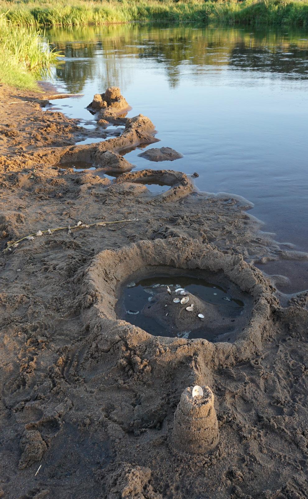 Mažytė smėlio pilis pilaitė, dekoruota kriauklelėmis, prie upės.