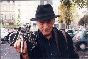 Su kamera rankoje ir skrybėle.