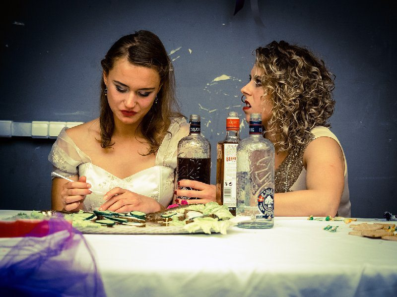 "Dvi aktorės su vestuvine apranga prie vestuvinio stalo spektaklyje ""Vestuvės""."
