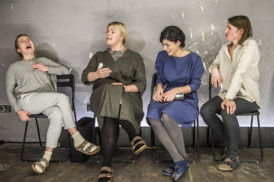 """Keturios aktorės sėdi ant kėdžių prie sienos spektaklyje """"Terapijos""""."""