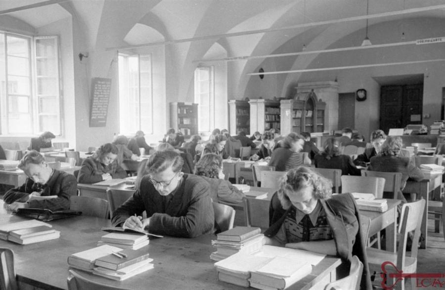 Studentai skaito bibliotekoje.