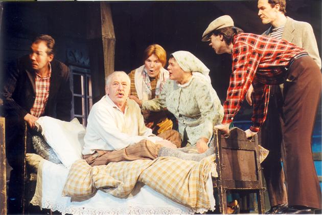 Vytautas Tomkus sėdi lovoje, aplink – kiti aktoriai.