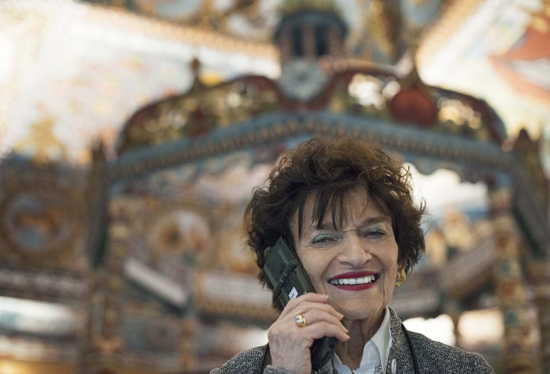 Šypsosi priglauduysi prie ausies telefoną.