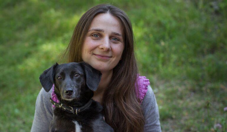 Pievoje mergina su juodu šuniuku