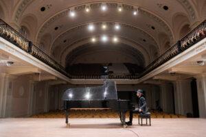 Sėdi prie fortepijono Filharmonijos salėje.