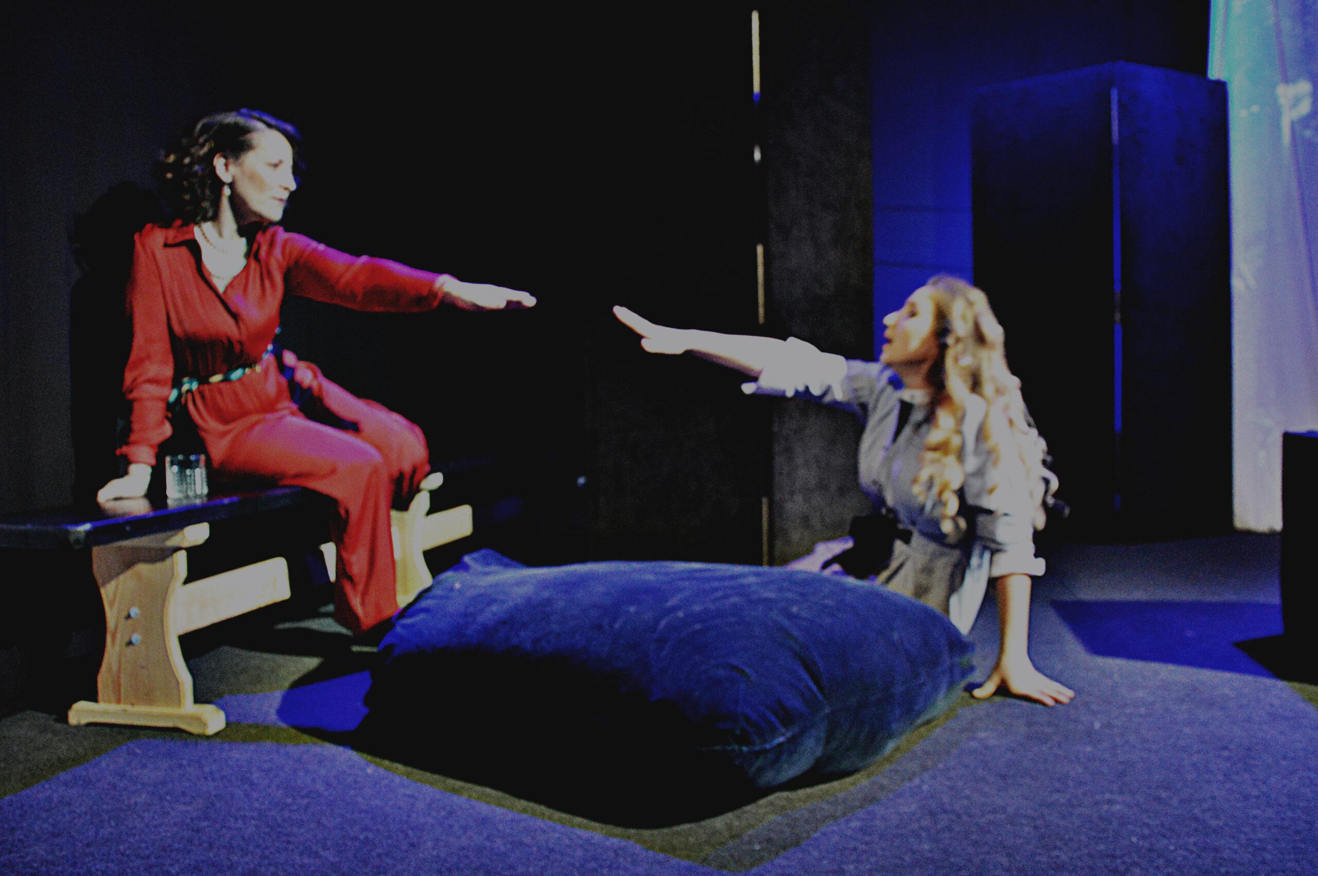 Spektaklio akimirka. Dvi moterys tiesia rankas viena į kitą