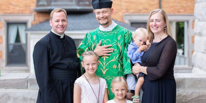Ką tik įšventintas diakonas T. Mackevičius Obl. OSB (centre) su žmona Asta ir vaikais Skaiste, Elija ir Rojumi bei klebonu tėvu Joshua Caswell, SJC. T. Mackevičiaus asmeninio archyvo nuotrauka