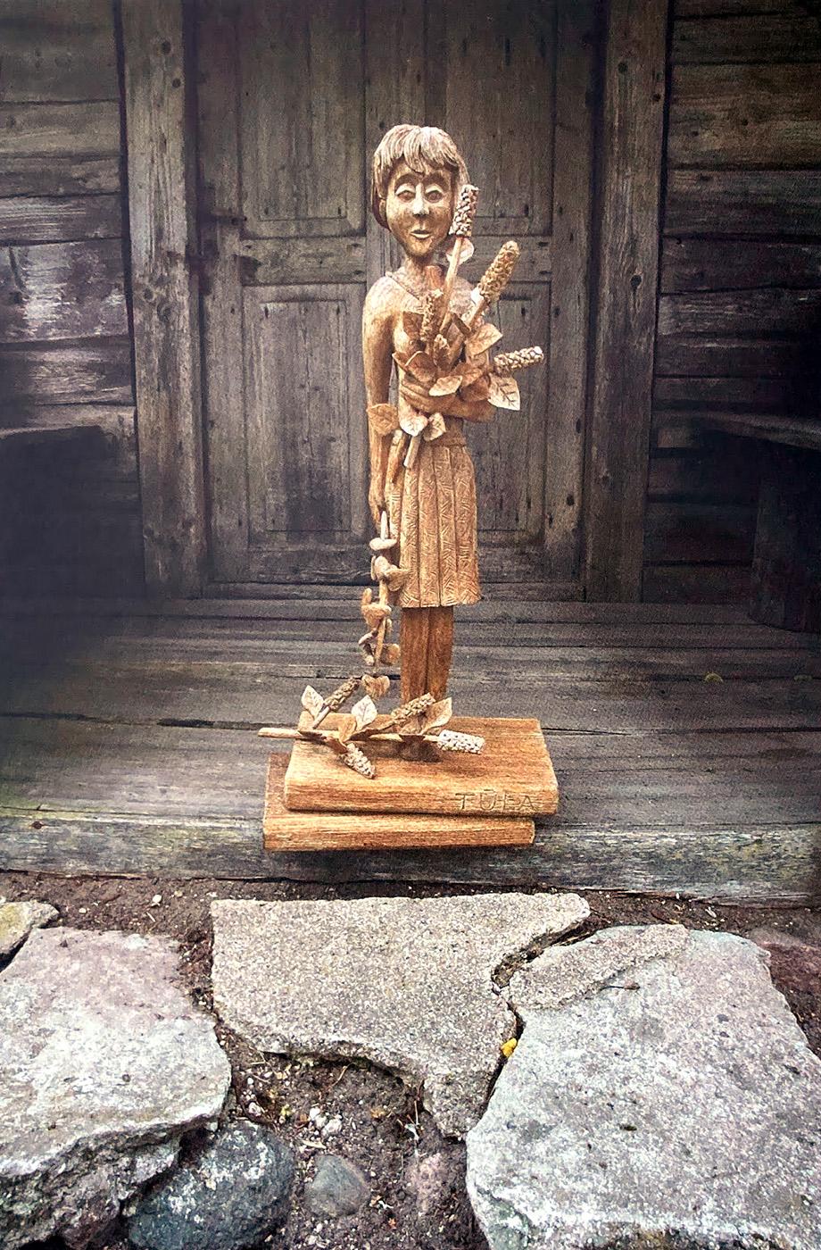 Mergaitės skulptūra prie medinių durų.