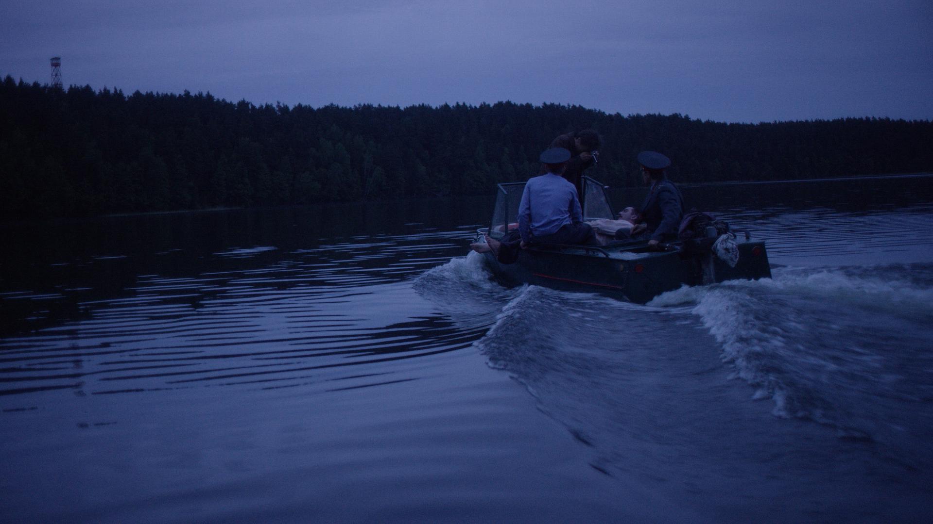 Plaukia ežere motorine valtimi milicininkai.