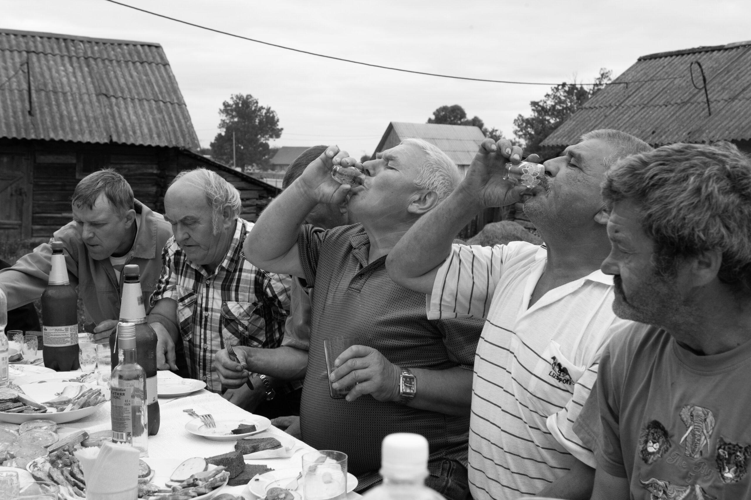 Pakėlę taureles vyrai geria prie stalo.
