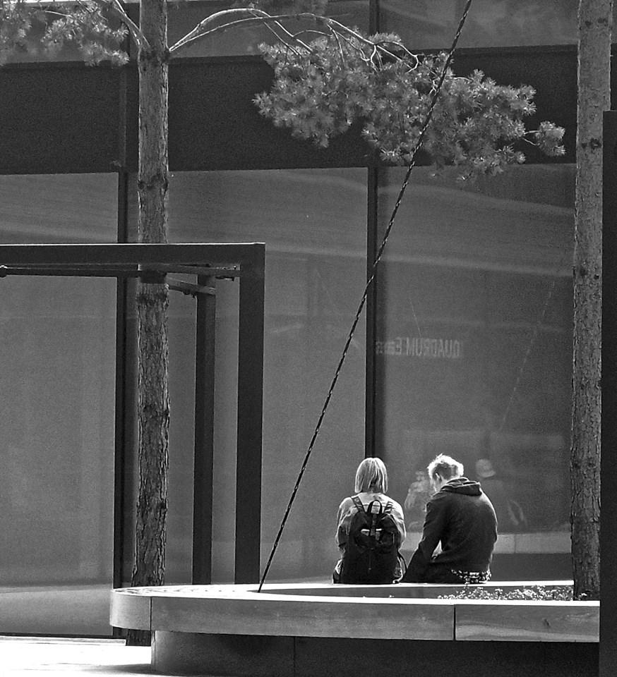 Sėdi du jauni žmonės prie medžio.