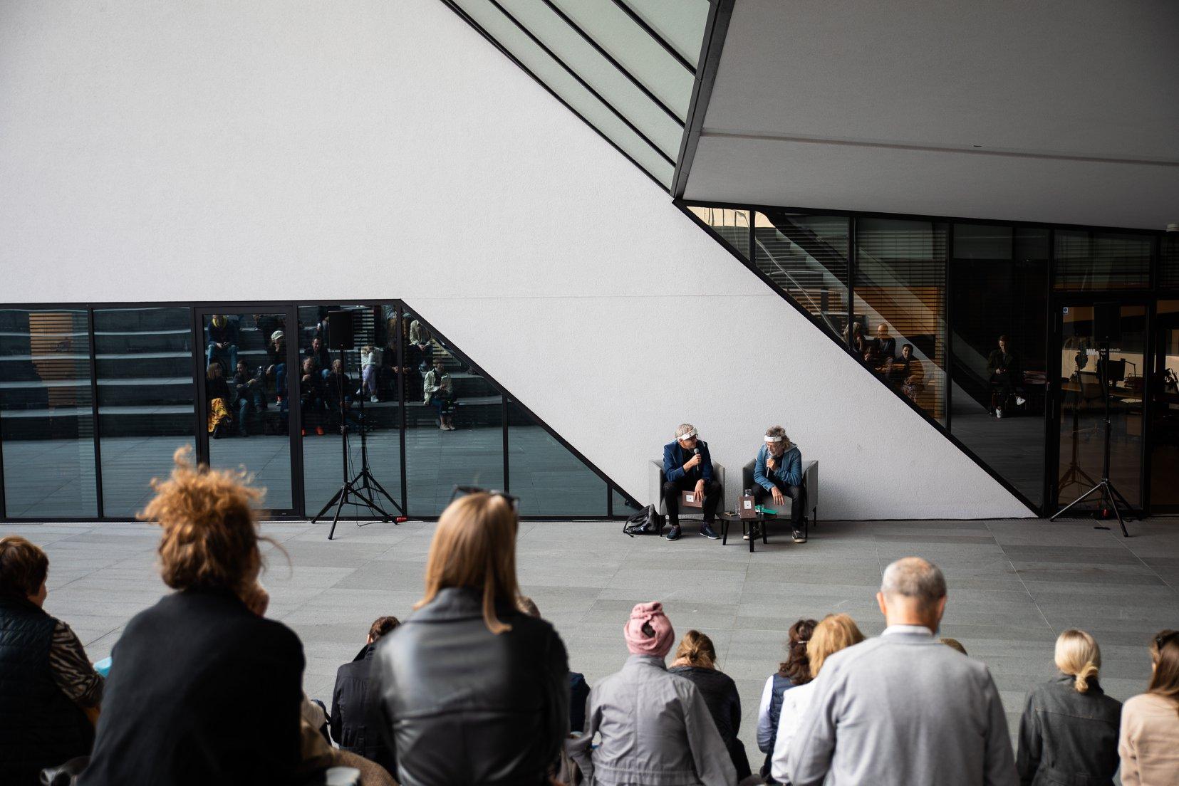 Žmonės prie muziejaus lauke.