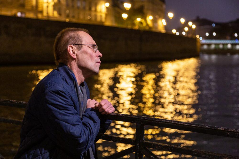 Valdas Papievis susimąstęs, apsikabinęs riešais Senos tilto turėklą. Vandenyje – naktinio miesto atspindžiai.