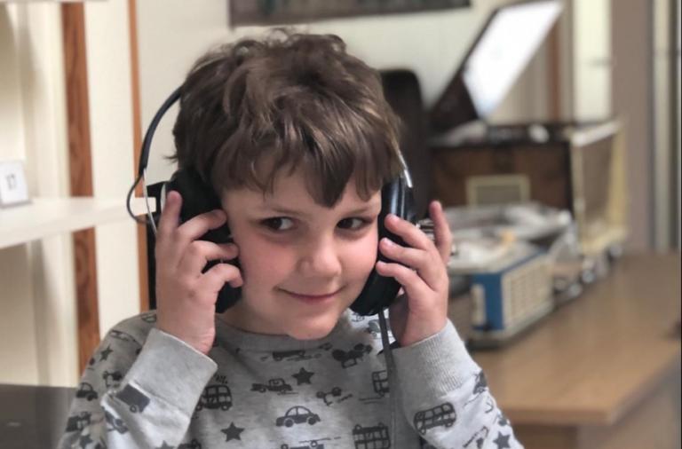 berniukas besiklausantis muzikos per ausines