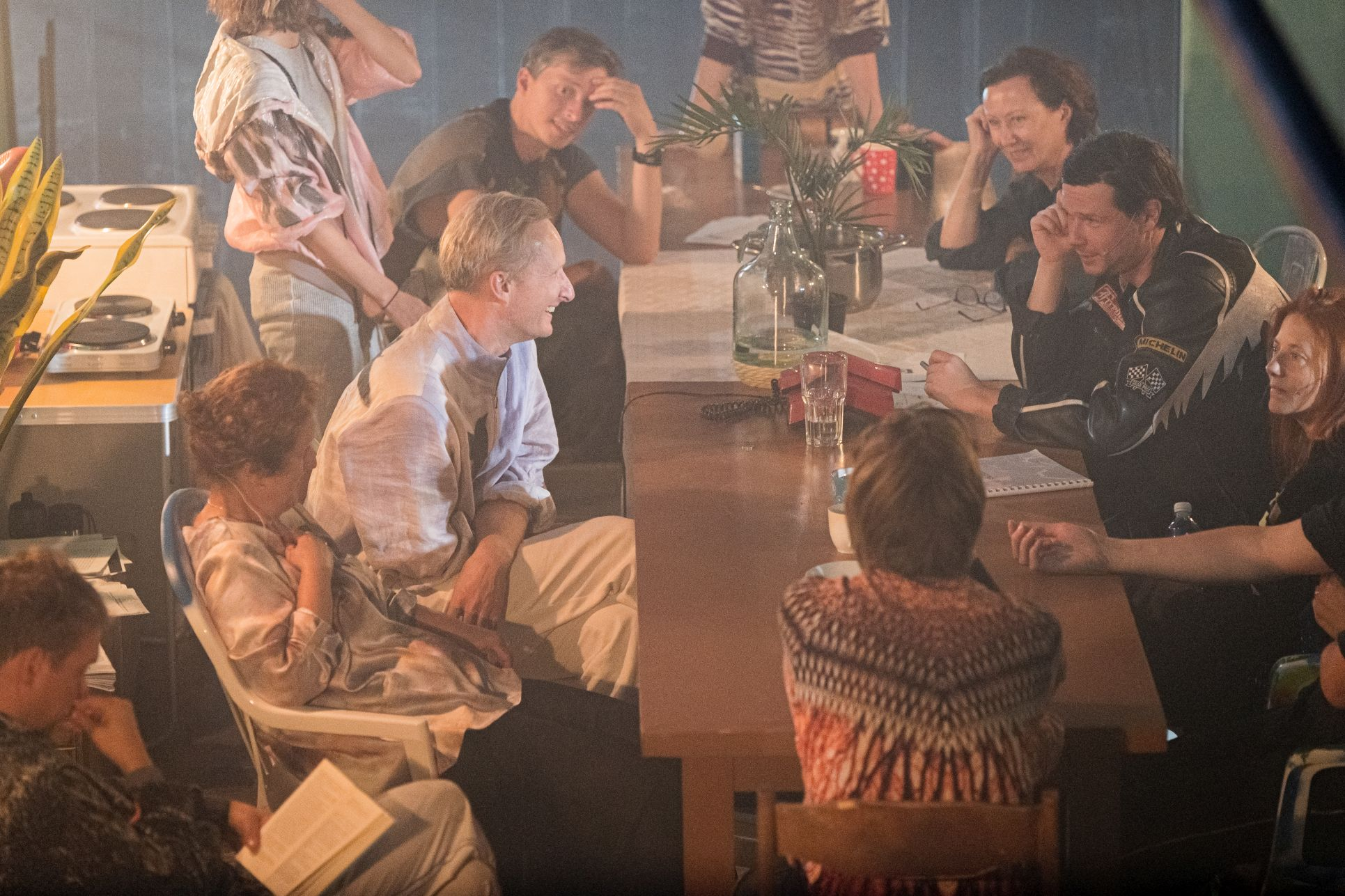 Aktoriai sėdi prie stalo.
