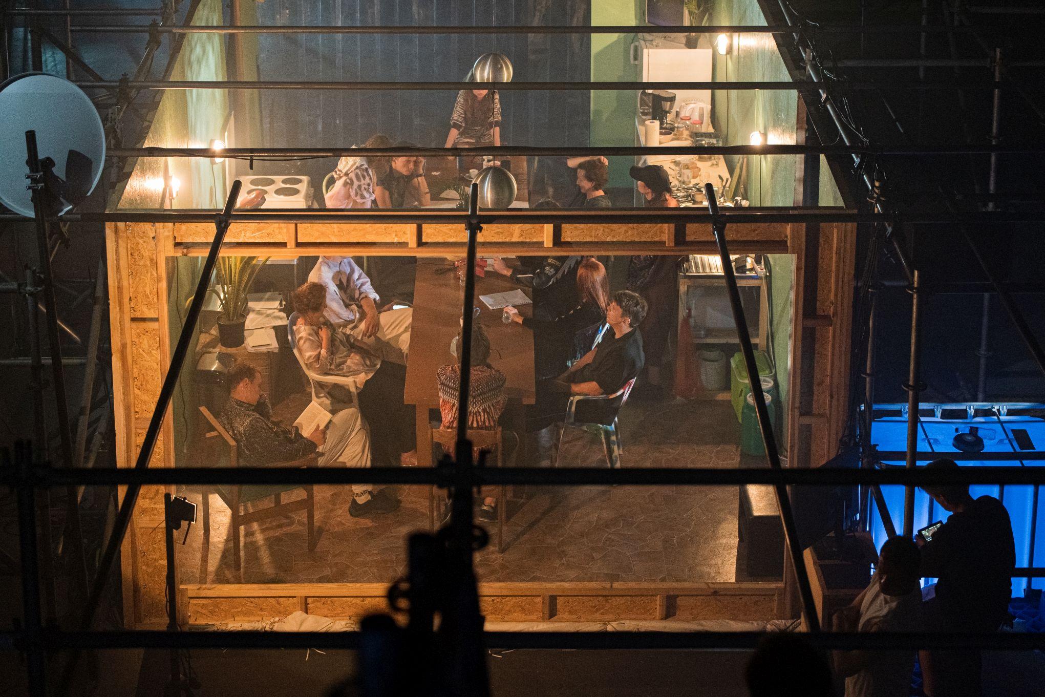 Aktoriai sėdi dėžutėje.